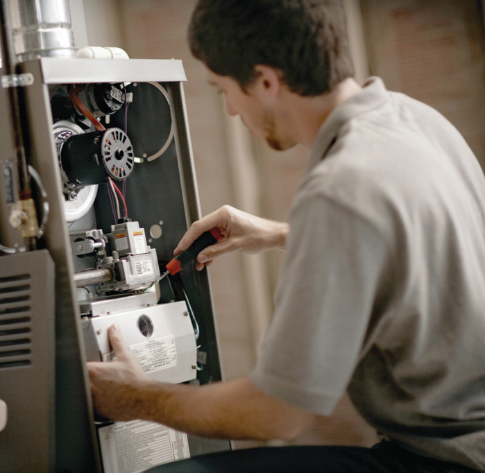 Image of technician perfoming a furnace repair