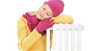Woman warming up near heating radiator
