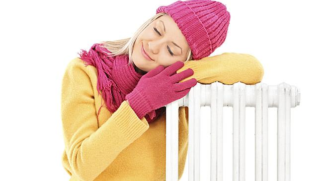 Woman warming up near heating radiator