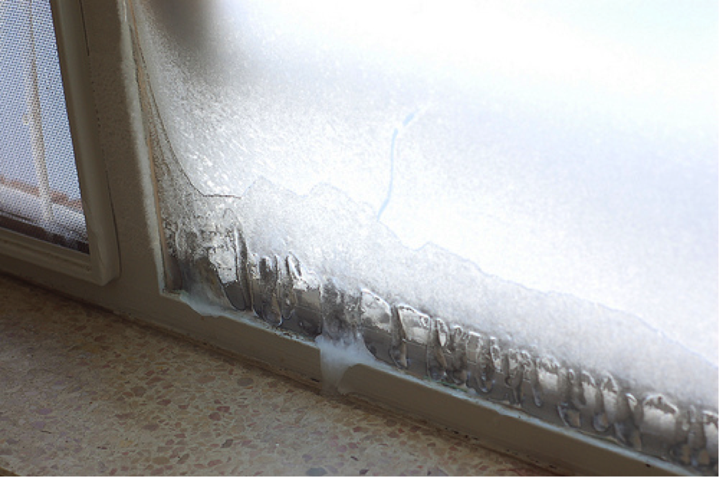 Image of a window with servere condensation and ice buidup