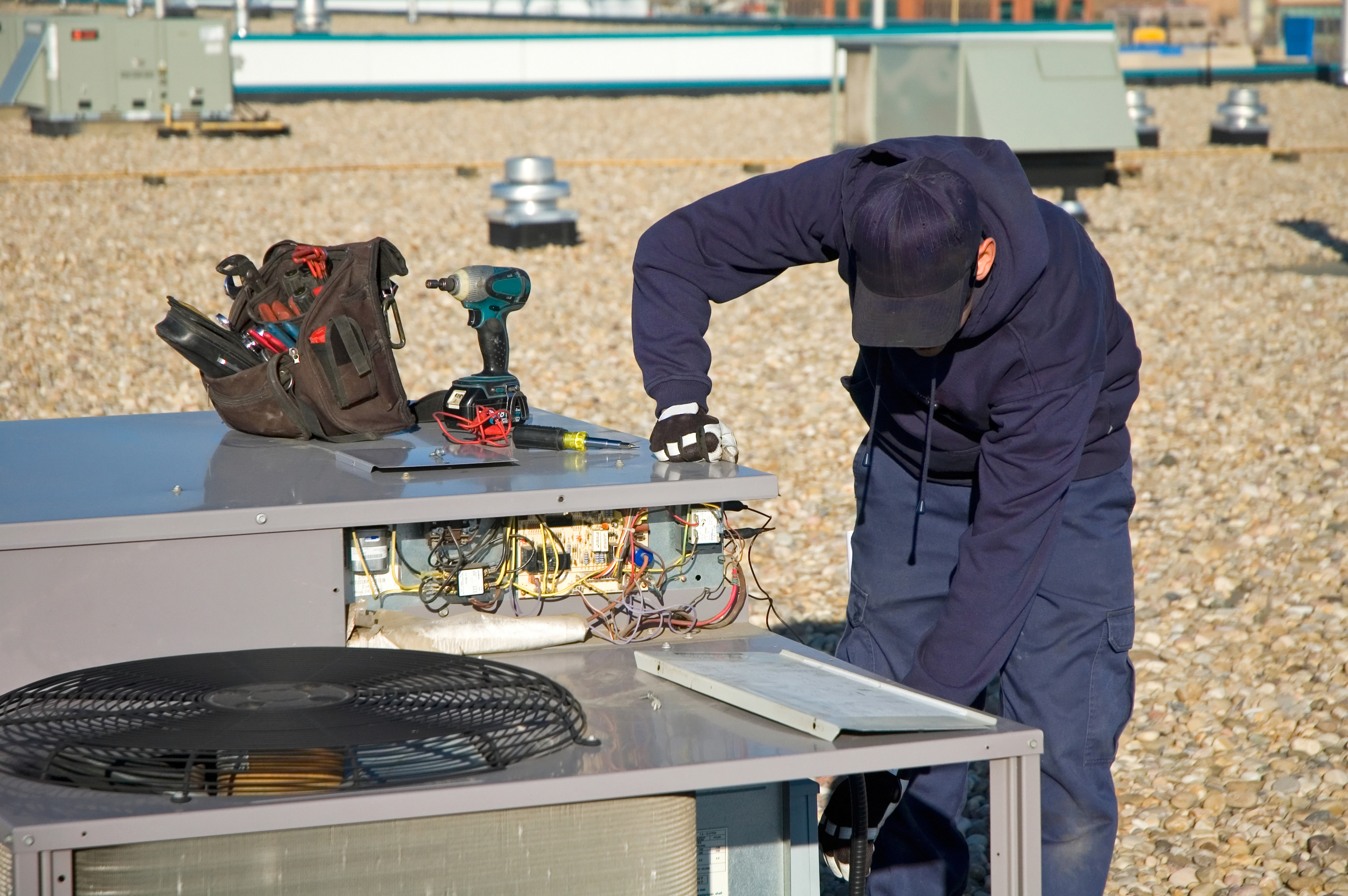Image of a technician servicing a commercial HVAC rooftop unit in Saskatoon