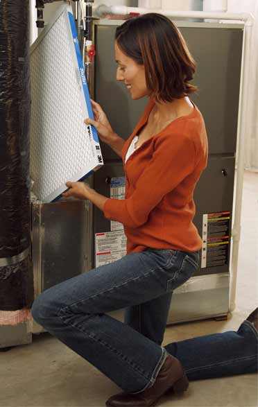 Image of client performing their own furnace troubleshooting and maintenance by changing the furnace filter