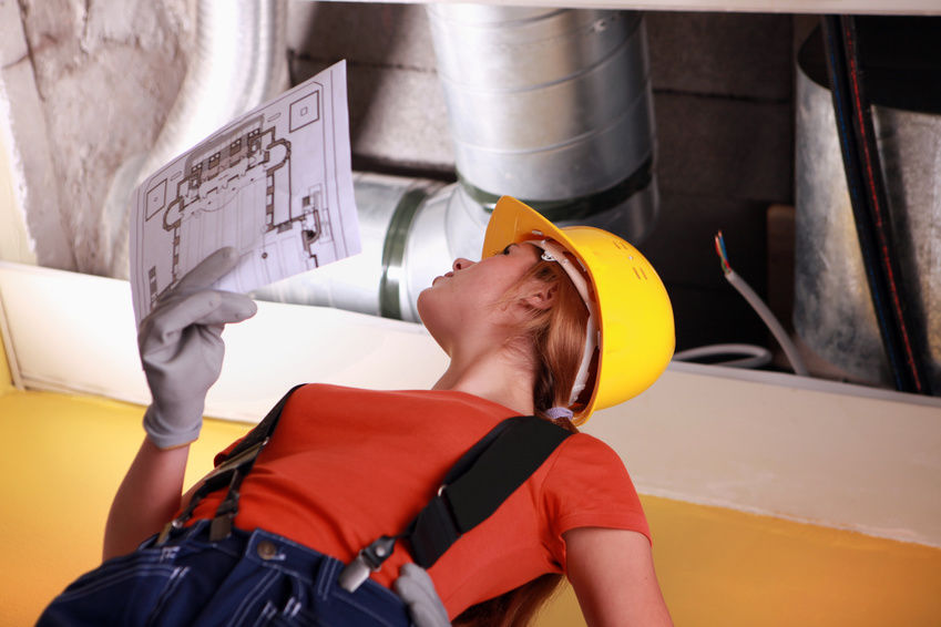 Woman installing air conditioning duct work