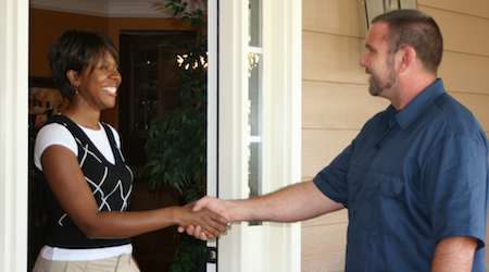 man shaking womans hand at the door