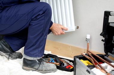 man fixing a radiator